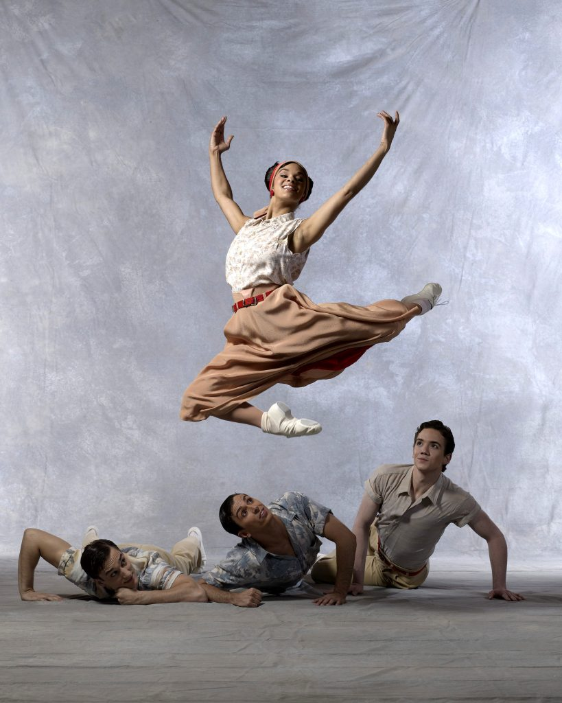 three male dancers on stage and one female in the air
