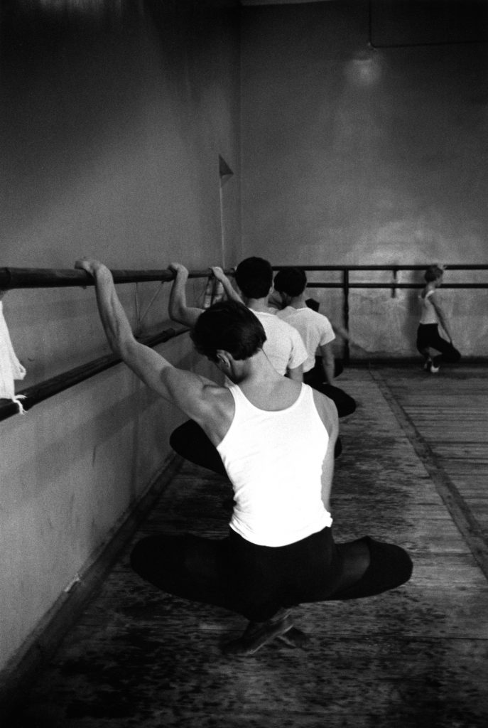 male ballet dancers warm up at the barre