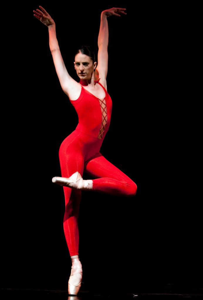 dancer on pointe in red all in one dance wear