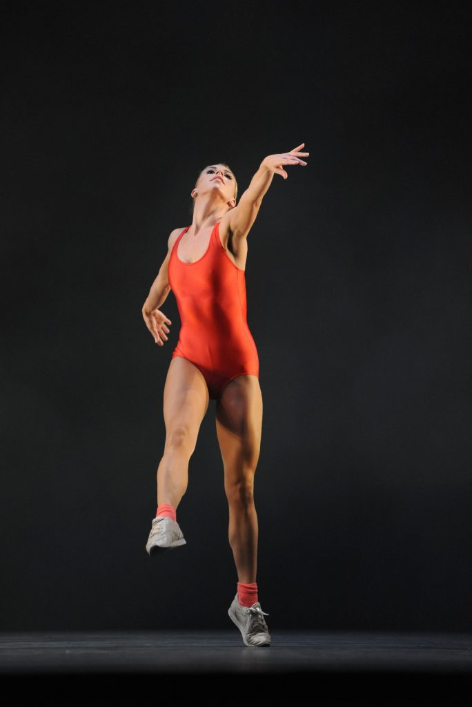 dancer in red leotard and trainers