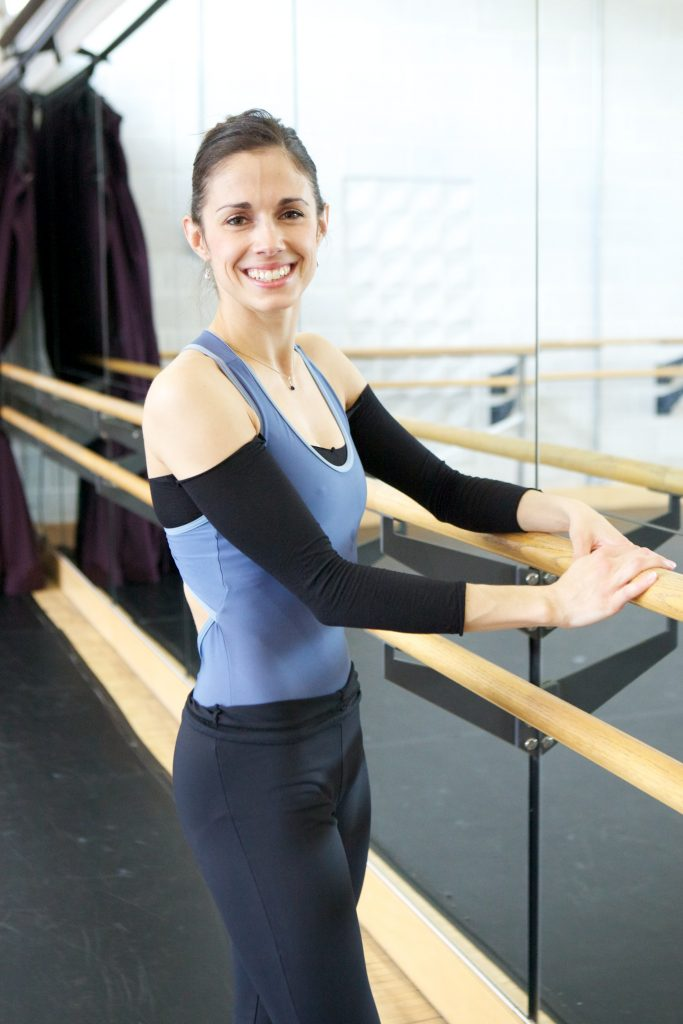 dancer stands next to the barre