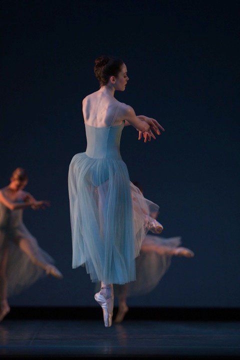 dancer in long blue dress on stage in pointe shoes