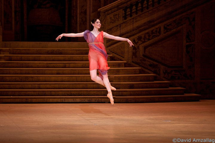 dancer in high jump in pointe shoes and red dress