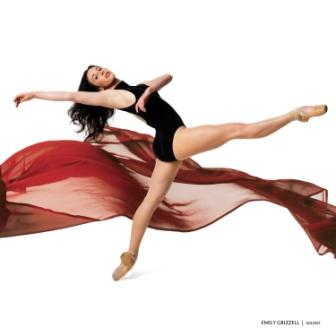 dancer in pointe shoes wearing a black leotard stands on one foot with red flowing ribbons behind her