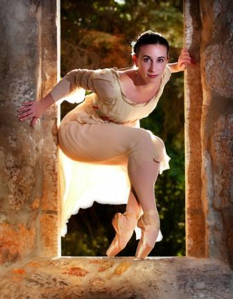 dancer stands on pointe looking through a door