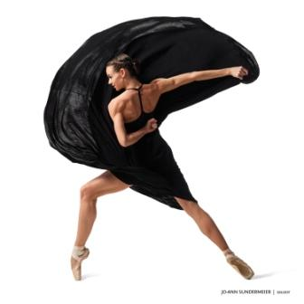 dancer poses with black cape
