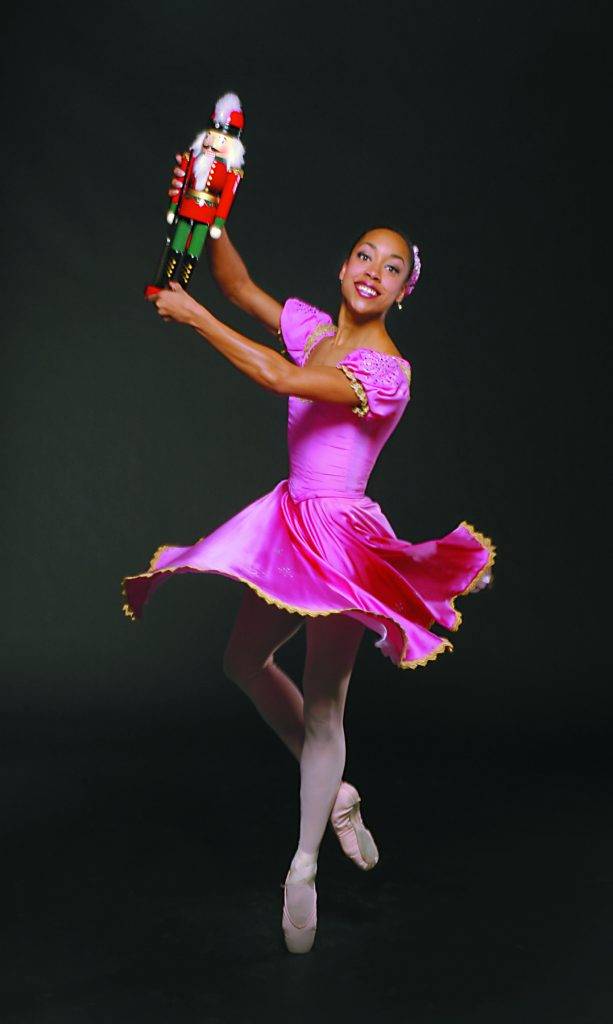 ballet dancer on pointe holding a nutcracker doll