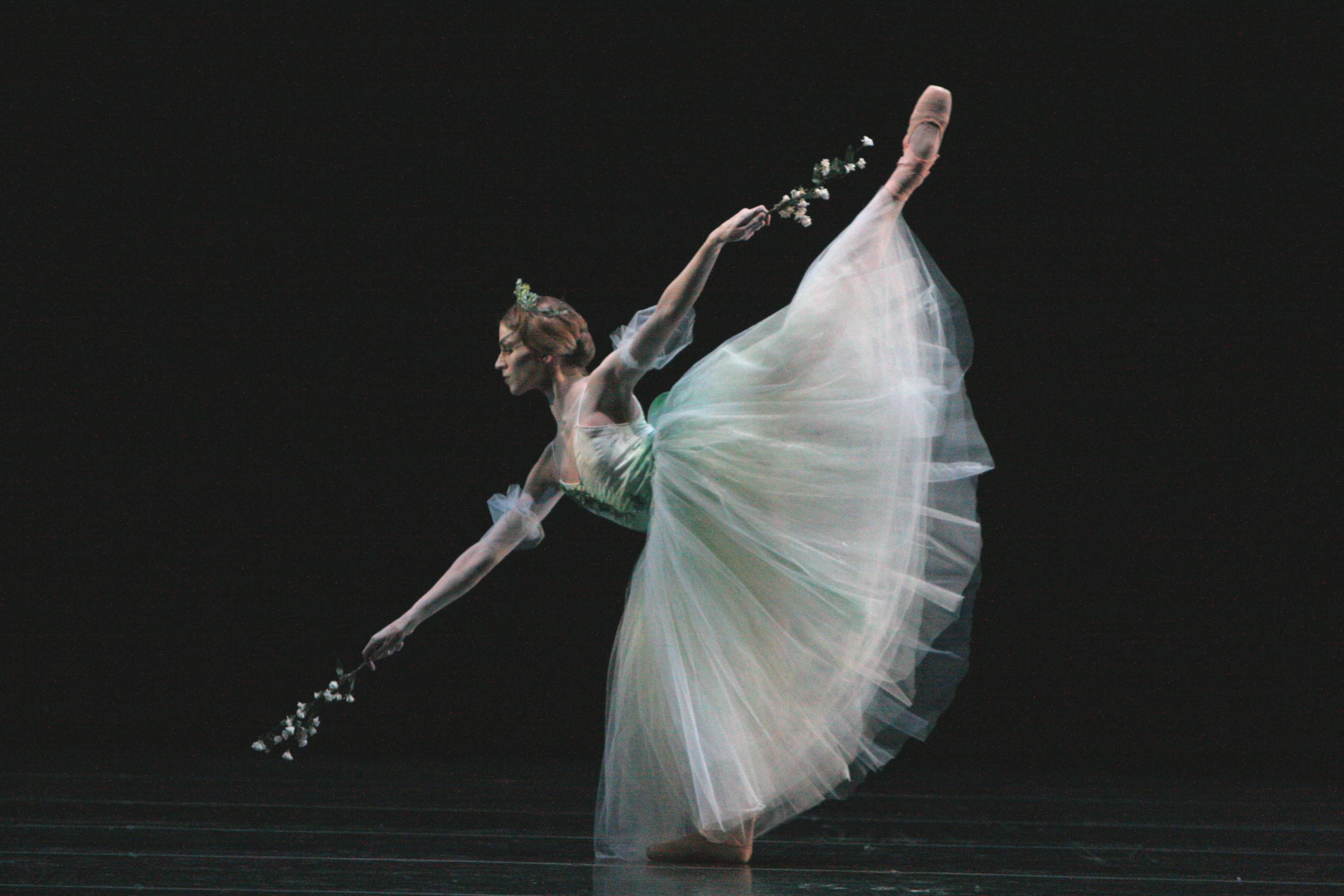 ballet dancer in long white dress bends on pointe