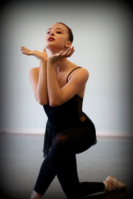 ballet dancer cups her head in her hands